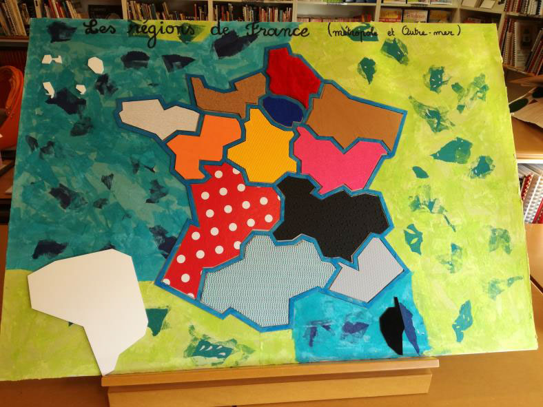 Photo d'une carte de France des régions. Les régions sont délimitées par un contour en carton. Chaque région est représentée par une texture différente : cuir, toile cirée, tissu, feutrine, carton granuleux... Les couleurs sont également variées.