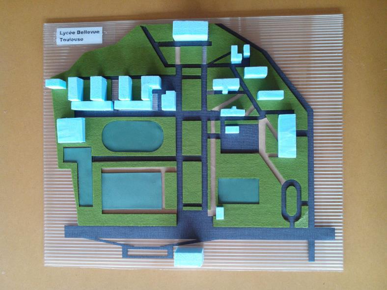 Photo du plan d'un lycée aux bâtiments très dispersés. Les espaces verts et les voies de circulations sont représentés en feutrine verte et en papier rugueux noirs découpés au laser. Les bâtiments, représentés en polystyrène, sont découpés manuellement.