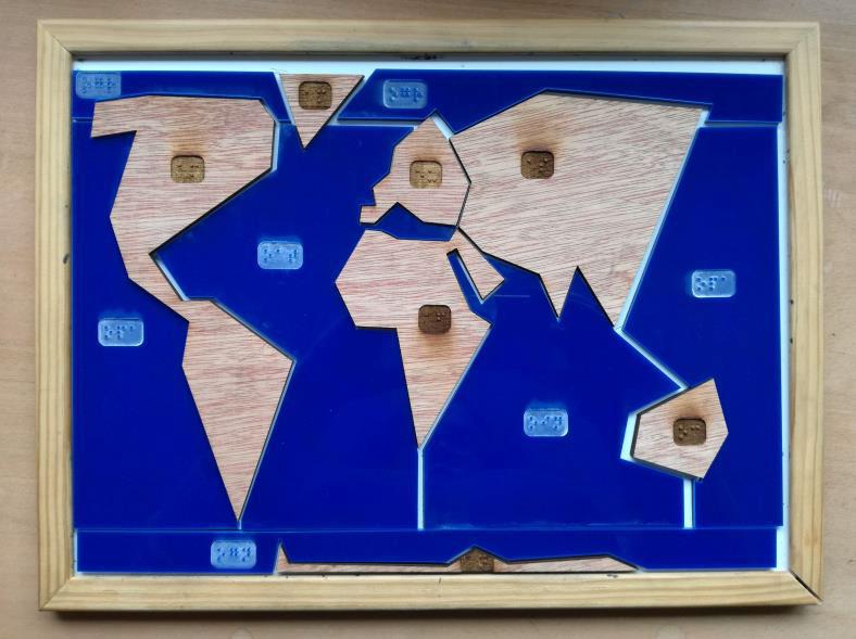 photo d'un puzzle planisphère découpé ultra simplifié, avec les continents en bois et les océans en plexiglas bleu.