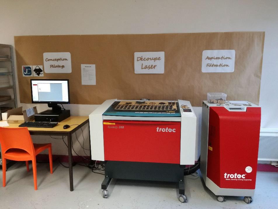 La découpeuse laser, parallélépipède de 80 cm de hauteur, est accompagnée d'un bloc d'aération et d'un PC de commande.