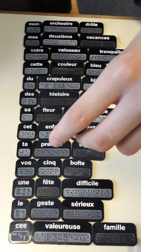 Photo montrant des tuiles portant des mots gravés en caractères agrandis et en braille, pour un jeu de français.