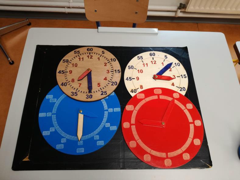 Photo montrant 4 horloges à manipuler, 2 en gros K (bois) et 2 en braille (plexiglas). La numérotation (heures et/ou minutes) et le nombre de graduations varient d'un modèle à l'autre.