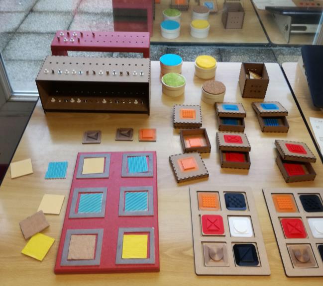 Photo montrant pluesieurs jeux adaptés, dont deux types de mémorys différents réalisés en impression 3D et en découpe laser, avec des encastrements pour créer des boites.