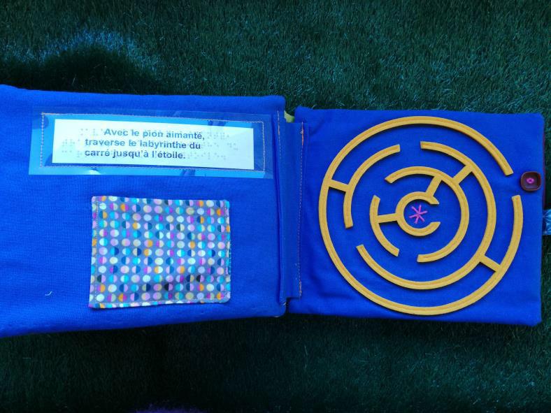 Photo montrant un l;ivre tactile en tissu ouvert à la page d'un labyrinthe rond découpé en feutrine. La consigne écrite est de gagner le centre du labyrinthe en partant d'un repère à l'extérieur.