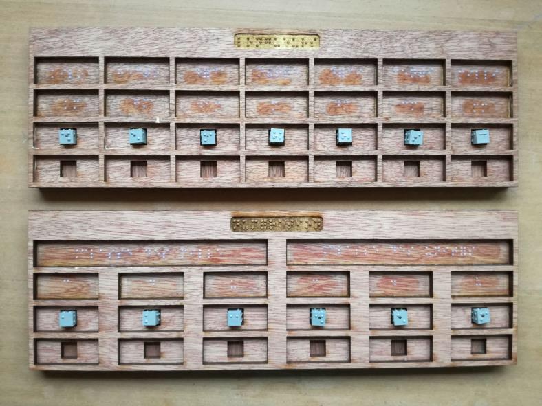 Photo montrant 2 tableaux en bois, matérialisant les colonnes des différentes unités (7 pour les longueurs, 6 pour la numération). Grâce à des emplacements carrés spécifiques dans chaque colonne, on peut disposes les cubarithmes dans les tableaux.